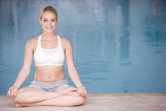 Woman sitting poolside doing yoga smiling Royalty Free Stock Photography