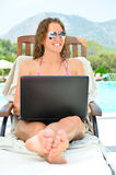 Woman is sitting at poolside with laptop Stock Photo