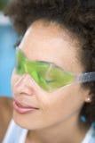 Woman sitting poolside using eye mask. With eyes shut stock images