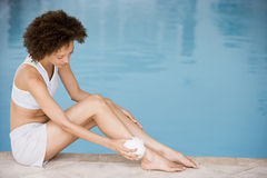 Woman sitting poolside using shower puff Royalty Free Stock Images