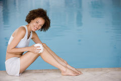 Woman sitting poolside using shower puff Stock Photo