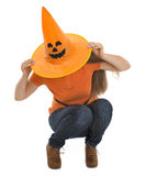 Woman sitting with pulled Halloween hat over head Royalty Free Stock Photos