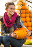 Woman sitting with pumpkin Stock Image