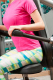 Woman sitting and pushing triceps machine in the gym Royalty Free Stock Images