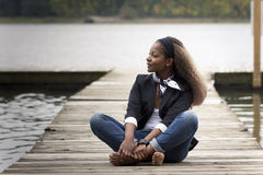 Woman sitting on quay Stock Images