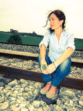 Woman sitting on a rail track Stock Photos