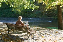 Woman sitting and reading on a bench in a park stock photography