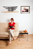 Woman sitting and reading a book. Woman is sitting on a sofa at home and reading a book. Image on the wall was photographed by me royalty free stock photo