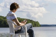Woman sitting an  reading on a chair by the Lake. Woman sitting on a chair by the lake reading a book Stock Image