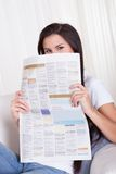 Woman sitting reading a newspaper Royalty Free Stock Image