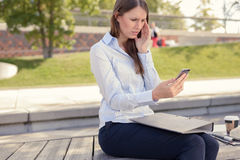 Woman sitting reading an sms with a worried look Royalty Free Stock Photography