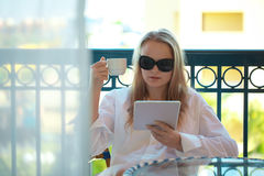 Woman sitting reading a tablet-pc on balcony Stock Image