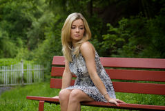 Woman sitting on a red bench in the garden Stock Photography
