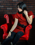 Woman sitting in red chair Royalty Free Stock Photos