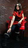 Woman sitting in red chair reaching down to her foot Stock Image