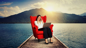 Woman sitting on the red chair on wood moorage. Tired businesswoman sitting on the red chair on wood moorage over beautiful landscape Stock Photography