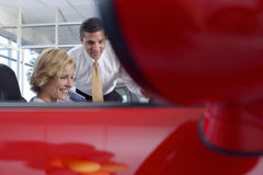 Woman sitting in red convertible car in showroom, salesman assisting, side view, focus on background Stock Photos