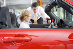 Woman sitting in red convertible car in showroom, salesman assisting, side view, focus on foreground Royalty Free Stock Image