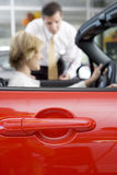 Woman sitting in red convertible car in showroom, salesman assisting, side view, focus on foreground Royalty Free Stock Photography