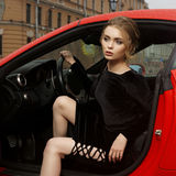 Woman sitting in red sport car. Young sexy beautiful woman in black dress sitting in red sport car Stock Images