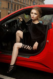 Woman sitting in red sport car. Young sexy beautiful woman in black dress sitting in red sport car Royalty Free Stock Photos