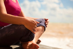 Woman sitting in relaxation yoga pose. At the sea beach. Closeup image stock image