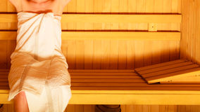 Woman sitting relaxed in wooden sauna Royalty Free Stock Image