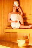 Woman sitting relaxed in wooden sauna Stock Photos