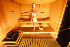 Woman sitting relaxed in wooden sauna Royalty Free Stock Images