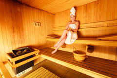 Woman sitting relaxed in wooden sauna Royalty Free Stock Photo