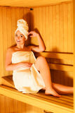 Woman sitting relaxed in wooden sauna Stock Images