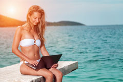 Woman sitting and relaxing on a beach with a laptop. Woman sitting and relaxing on a beach during holiday with a laptop royalty free stock image