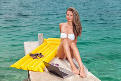 Woman sitting and relaxing on a beach with a laptop. Woman sitting and relaxing on a beach during holiday with a laptop stock images