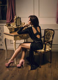 Woman sitting on a retro chair. Beautiful brunette woman sitting on a retro chair in gorgeous luxury black dress Stock Image