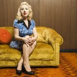 Woman sitting on retro couch. Stock Image