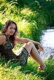 Woman sitting on riverside Royalty Free Stock Image
