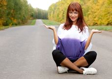 Woman is sitting on the road Stock Image