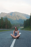 Woman sitting on the road Stock Image