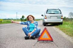 Woman sitting on road near emergency sign showing thumbs up Stock Photo