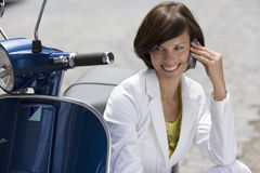 Woman sitting by roadside beside scooter, using mobile phone, smiling, close-up Stock Photography