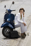 Woman sitting by roadside beside scooter, using mobile phone, smiling, disposable cup on kerb Stock Photography