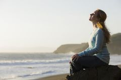 Woman Sitting on Rock. Portrait of a Pretty Redhead Woman Sitting on a Rock at The Ocean Royalty Free Stock Photography