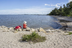 Woman sitting on a rock on the beach gazing out across  the lake Stock Photography