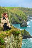 Woman sitting on rock cliff looking to ocean Co. Cork Ireland Stock Photos