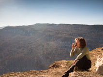 Woman sitting on a rock and drinking from a cup. On the background of sky Stock Photos