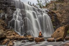 Woman sitting on a rock in front of Mackenzie Falls. Woman sitting on a rock in front of waterfall, Mackenzie Falls, The Grampians, Australia stock photos
