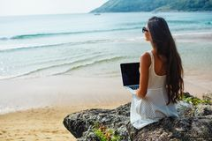Woman sitting on the rock with laptop Royalty Free Stock Photos