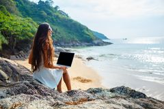 Woman sitting on the rock with laptop Stock Image