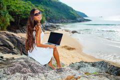 Woman sitting on the rock with laptop Stock Photo