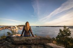 Woman sitting on a rock looking at the fjord and the city in Kristiansand. Stock Photo
